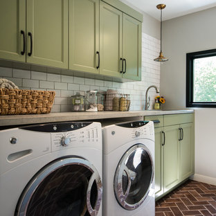 Example of a mid-sized transitional single-wall brick floor dedicated laundry room design in Detroit with an undermount sink, recessed-panel cabinets, green cabinets, concrete countertops, gray walls and a side-by-side washer/dryer