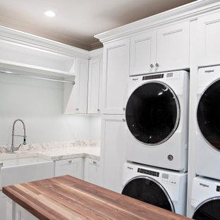 Inredning av ett klassiskt mycket stort vit l-format vitt grovkök, med en undermonterad diskho, släta luckor, vita skåp, bänkskiva i kvarts, flerfärgad stänkskydd, blå väggar, klinkergolv i keramik, en tvättpelare och brunt golv