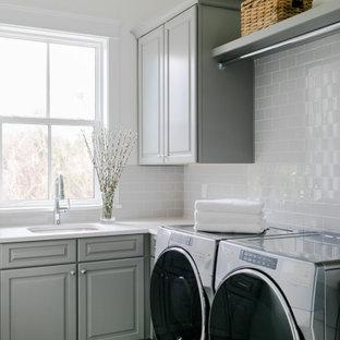 Idéer för mellanstora maritima l-formade grått grovkök, med en undermonterad diskho, luckor med upphöjd panel, grå skåp, vita väggar, en tvättmaskin och torktumlare bredvid varandra och grått golv