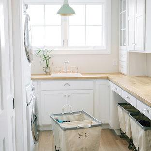 Exemple d'une buanderie chic en U dédiée avec un évier posé, un placard à porte shaker, des portes de placard blanches, un mur blanc, des machines superposées et un plan de travail beige.