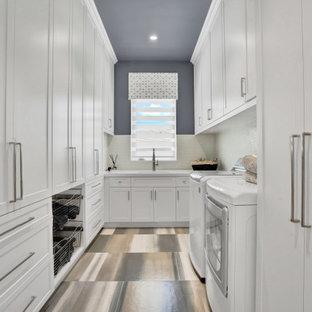 Пример оригинального дизайна: большая отдельная, п-образная прачечная в современном стиле с врезной раковиной, фасадами в стиле шейкер, белыми фасадами, столешницей из акрилового камня, белым фартуком, фартуком из мрамора, синими стенами, полом из керамической плитки, со стиральной и сушильной машиной рядом, синим полом и белой столешницей