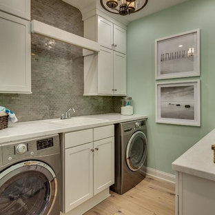 This is an example of a medium sized nautical galley utility room in Miami with a built-in sink, shaker cabinets, white cabinets, green walls, light hardwood flooring, composite countertops, a side by side washer and dryer, beige floors and white worktops.