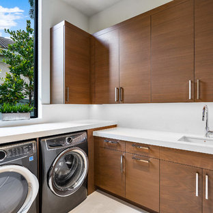 Design ideas for a large contemporary l-shaped separated utility room in Miami with a submerged sink, flat-panel cabinets, medium wood cabinets, white walls, marble flooring, a side by side washer and dryer, white floors and white worktops.