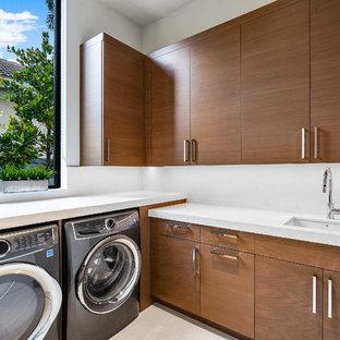 Foto på en stor funkis vita l-formad tvättstuga enbart för tvätt, med en undermonterad diskho, släta luckor, skåp i mellenmörkt trä, vita väggar, marmorgolv, en tvättmaskin och torktumlare bredvid varandra och vitt golv