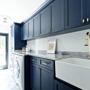 Idéer för att renovera en medelhavsstil grå linjär grått tvättstuga, med en rustik diskho, skåp i shakerstil, marmorbänkskiva, vita väggar och en tvättmaskin och torktumlare bredvid varandra