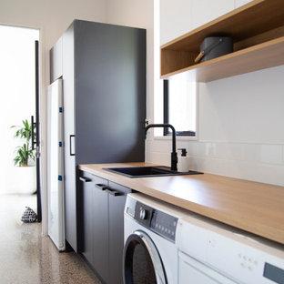 Esempio di una lavanderia multiuso moderna di medie dimensioni con lavello da incasso, ante lisce, ante nere, top in laminato, pareti bianche, pavimento in cemento e lavatrice e asciugatrice affiancate