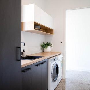 Immagine di una lavanderia multiuso minimalista di medie dimensioni con lavello da incasso, ante lisce, ante nere, top in laminato, pareti bianche, pavimento in cemento e lavatrice e asciugatrice affiancate
