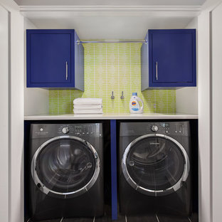 Small transitional black floor laundry room photo in New York with flat-panel cabinets, blue cabinets and green walls