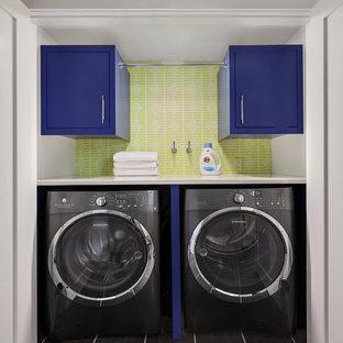 Ispirazione per una piccola lavanderia tradizionale con ante lisce, ante blu, pareti verdi, lavatrice e asciugatrice affiancate e pavimento nero
