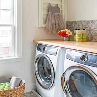 Exemple d'une buanderie chic dédiée et de taille moyenne avec un plan de travail en bois, un sol en carrelage de porcelaine, le lave-linge et le sèche-linge forment un seul appareil électroménager et un plan de travail marron.
