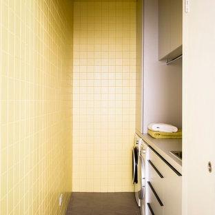 На фото: маленькая отдельная, параллельная прачечная в современном стиле с накладной раковиной, плоскими фасадами, серыми фасадами, столешницей из ламината, желтыми стенами, полом из керамогранита и со стиральной и сушильной машиной рядом