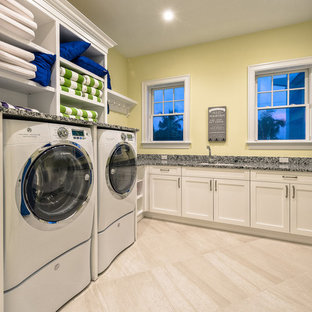 Large classic u-shaped utility room in Miami with a submerged sink, white cabinets, granite worktops, yellow walls, ceramic flooring and a side by side washer and dryer.