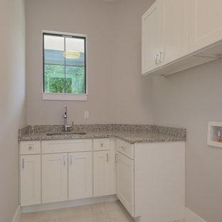 Bild på en mellanstor funkis flerfärgade l-formad flerfärgat tvättstuga enbart för tvätt, med grå väggar, klinkergolv i porslin, beiget golv, en undermonterad diskho, skåp i shakerstil, vita skåp, granitbänkskiva och en tvättmaskin och torktumlare bredvid varandra