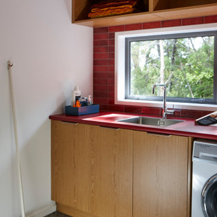 Photo of a large contemporary single-wall separated utility room in Auckland with a side by side washer and dryer and red worktops.