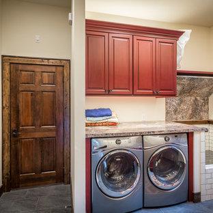 Ispirazione per un'ampia lavanderia multiuso rustica con lavello da incasso, ante con bugna sagomata, ante rosse, top in laminato, pareti beige, pavimento con piastrelle in ceramica e lavatrice e asciugatrice affiancate