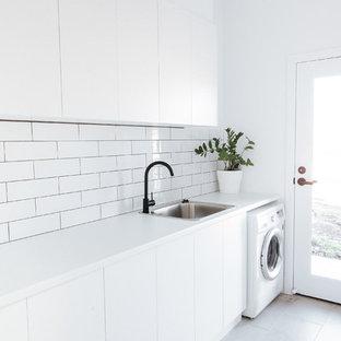 Modern inredning av en mellanstor vita linjär vitt tvättstuga enbart för tvätt, med en nedsänkt diskho, släta luckor, vita skåp, laminatbänkskiva, vita väggar, grått golv och laminatgolv