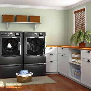 Inspiration för en mellanstor funkis bruna l-formad brunt tvättstuga enbart för tvätt, med skåp i shakerstil, vita skåp, träbänkskiva, gröna väggar, mellanmörkt trägolv, en tvättmaskin och torktumlare bredvid varandra och brunt golv