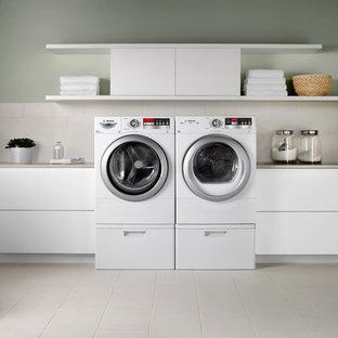 Inspiration för mellanstora moderna linjära tvättstugor enbart för tvätt, med släta luckor, vita skåp, bänkskiva i koppar, grå väggar, klinkergolv i keramik, en tvättmaskin och torktumlare bredvid varandra och beiget golv