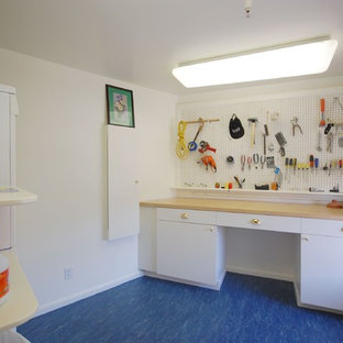 Dedicated laundry room - mid-sized traditional blue floor and linoleum floor dedicated laundry room idea in Boston with flat-panel cabinets, white cabinets, white walls, a stacked washer/dryer and wood countertops