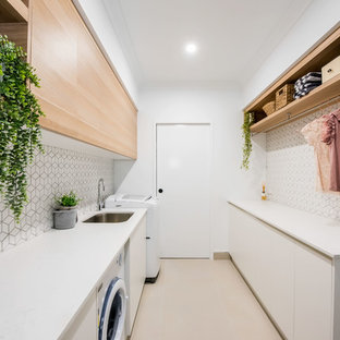 Inspiration for a mid-sized contemporary galley dedicated laundry room in Other with an undermount sink, flat-panel cabinets, white walls, a side-by-side washer and dryer, white benchtop, light wood cabinets, granite benchtops, white splashback, ceramic splashback, ceramic floors and white floor.
