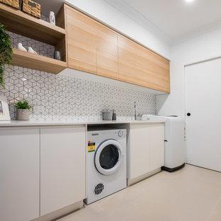 Inredning av en modern mellanstor vita parallell vitt tvättstuga enbart för tvätt, med en undermonterad diskho, släta luckor, skåp i ljust trä, granitbänkskiva, vitt stänkskydd, stänkskydd i keramik, vita väggar, klinkergolv i keramik, en tvättmaskin och torktumlare bredvid varandra och vitt golv