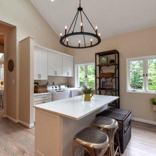 Idéer för vintage parallella vitt tvättstugor, med skåp i shakerstil, vita skåp, beige väggar, mellanmörkt trägolv, en tvättmaskin och torktumlare bredvid varandra och brunt golv