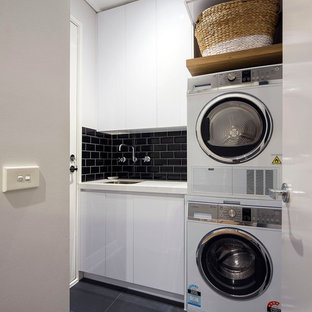 Inspiration for a small contemporary single-wall ceramic floor and gray floor dedicated laundry room remodel in Melbourne with white cabinets, granite countertops, a stacked washer/dryer, an undermount sink, flat-panel cabinets and gray walls