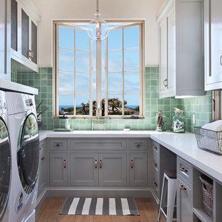 Immagine di una sala lavanderia mediterranea con ante in stile shaker, ante grigie, lavatrice e asciugatrice affiancate, pavimento marrone e top bianco