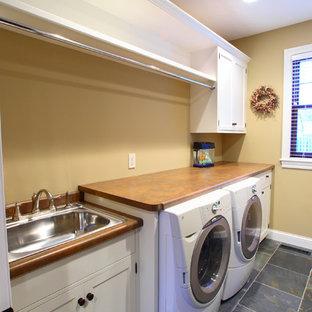 Inspiration för en stor amerikansk linjär tvättstuga enbart för tvätt, med en nedsänkt diskho, släta luckor, vita skåp, laminatbänkskiva, skiffergolv, en tvättmaskin och torktumlare bredvid varandra och bruna väggar