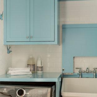 Aménagement d'une petit buanderie linéaire classique dédiée avec un évier utilitaire, un placard à porte shaker, des portes de placard bleues, un plan de travail en bois, un mur blanc, un sol en bois brun, des machines côte à côte, un sol marron et un plan de travail bleu.