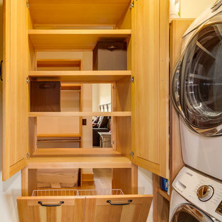 Small transitional l-shaped laundry room photo in Denver with open cabinets and a stacked washer/dryer
