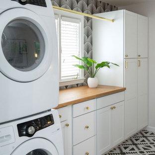 Immagine di una sala lavanderia tradizionale di medie dimensioni con ante in stile shaker, ante bianche, top in legno, pareti bianche, pavimento con piastrelle in ceramica, lavatrice e asciugatrice a colonna, pavimento nero, top marrone e carta da parati