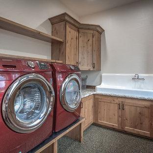 Immagine di una lavanderia multiuso rustica di medie dimensioni con lavello stile country, ante in stile shaker, ante in legno scuro, top in granito, pareti bianche, pavimento in pietra calcarea e lavatrice e asciugatrice affiancate