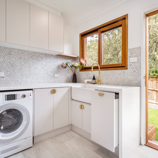 Inspiration for a mid-sized contemporary l-shaped laundry room in Melbourne with a farmhouse sink, flat-panel cabinets, quartz benchtops, white walls, porcelain floors, a side-by-side washer and dryer, grey floor, white benchtop and beige cabinets.