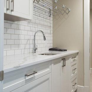 Inredning av en klassisk mellanstor linjär tvättstuga enbart för tvätt, med en undermonterad diskho, luckor med infälld panel, vita skåp, marmorbänkskiva, beige väggar och ljust trägolv