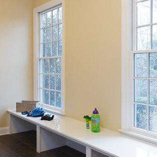 Idées déco pour une grande buanderie parallèle moderne multi-usage avec un évier 1 bac, un placard à porte plane, des portes de placard blanches, un plan de travail en quartz modifié, un mur jaune, un sol en bois foncé, des machines côte à côte, un sol marron et un plan de travail blanc.