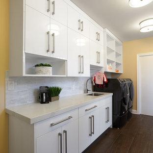 Bild på ett stort funkis vit parallellt vitt grovkök, med en enkel diskho, släta luckor, vita skåp, bänkskiva i kvarts, gula väggar, mörkt trägolv, en tvättmaskin och torktumlare bredvid varandra och brunt golv