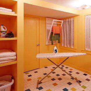 Inspiration för en mellanstor funkis tvättstuga enbart för tvätt, med en allbänk, luckor med upphöjd panel, vita skåp, orange väggar, klinkergolv i keramik och en tvättmaskin och torktumlare bredvid varandra