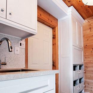 Foto de cuarto de lavado lineal, bohemio, pequeño, con armarios estilo shaker, puertas de armario blancas, encimera de cuarzo compacto, lavadora y secadora apiladas, fregadero bajoencimera, paredes marrones y suelo de baldosas de porcelana