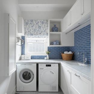 Immagine di una piccola lavanderia multiuso classica con lavello da incasso, ante a filo, ante bianche, top in marmo, pareti blu, pavimento con piastrelle in ceramica, lavasciuga, pavimento multicolore e top bianco