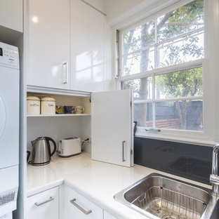 This is an example of a small modern l-shaped utility room in Melbourne with a double-bowl sink, flat-panel cabinets, white cabinets, laminate benchtops, white walls, light hardwood floors and a stacked washer and dryer.