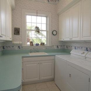 Bild på en mellanstor vintage turkosa u-formad turkost tvättstuga enbart för tvätt, med en nedsänkt diskho, luckor med infälld panel, vita skåp, laminatbänkskiva, vita väggar, klinkergolv i keramik och en tvättmaskin och torktumlare bredvid varandra