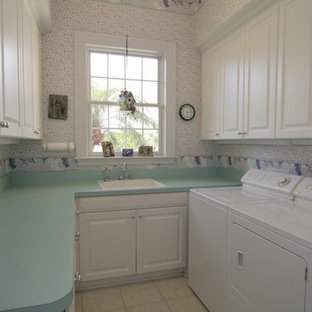 This is an example of a mid-sized traditional u-shaped dedicated laundry room in Tampa with a drop-in sink, recessed-panel cabinets, white cabinets, laminate benchtops, white walls, ceramic floors, a side-by-side washer and dryer and turquoise benchtop.