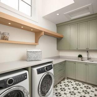 Inspiration för klassiska l-formade grått tvättstugor enbart för tvätt, med en undermonterad diskho, luckor med infälld panel, gröna skåp, bänkskiva i kvarts, vita väggar, marmorgolv, en tvättmaskin och torktumlare bredvid varandra och vitt golv