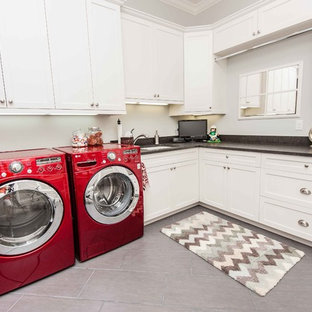 Inspiration for a timeless gray floor laundry room remodel in Orlando with white cabinets and an undermount sink