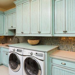 Inredning av en rustik stor parallell tvättstuga enbart för tvätt, med en undermonterad diskho, blå skåp, beige väggar, en tvättmaskin och torktumlare bredvid varandra, luckor med profilerade fronter, kaklad bänkskiva och klinkergolv i keramik