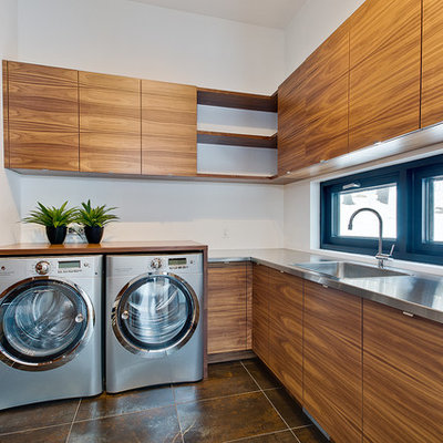 Example of a trendy l-shaped brown floor dedicated laundry room design in Montreal with a drop-in sink, flat-panel cabinets, medium tone wood cabinets, stainless steel countertops, white walls, a side-by-side washer/dryer and gray countertops