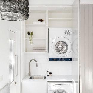 Idéer för att renovera en liten vita linjär vitt tvättstuga enbart för tvätt, med en nedsänkt diskho, skåp i shakerstil, beige skåp, marmorbänkskiva, vitt stänkskydd, stänkskydd i marmor, vita väggar, ljust trägolv, en tvättpelare och beiget golv