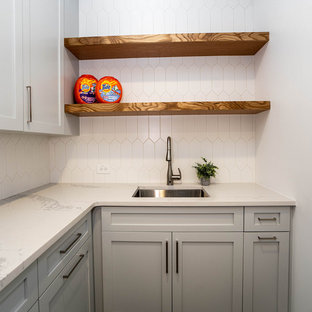 Inspiration for a mid-sized contemporary l-shaped porcelain tile and gray floor dedicated laundry room remodel in Atlanta with an undermount sink, shaker cabinets, gray cabinets, quartz countertops, gray walls, a side-by-side washer/dryer and white countertops