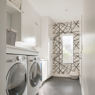 Example of a small trendy porcelain tile, gray floor and wallpaper laundry room design in Austin with flat-panel cabinets, white cabinets, a side-by-side washer/dryer, multicolored walls and white countertops
